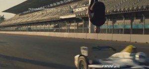Stuntman macht einen Rückwärtssalto über einen heranrasenden E-Rennwagen
